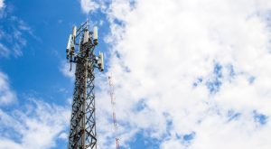 Image of cell tower with cloudy but bright blue sky in the background