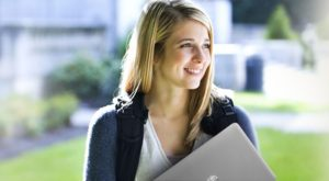 a female student holding a laptop
