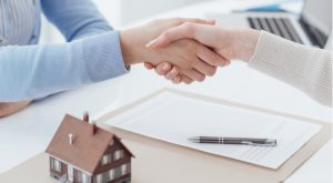 two people shaking hands over a desk with mortgage papers and a small model of a house