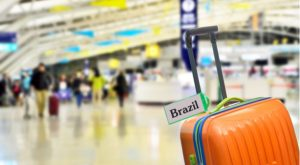 orange luggage in an airport with the word Brazil on it