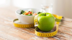 a bowl of vegetables, a green apple, and a measuring tape sit on a wooden table