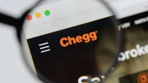 Chegg (CHGG) logo on the company's web page magnified by a magnifying glass