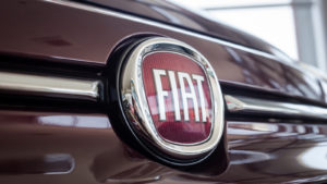 A close-up shot of the Fiat (FCAU) logo on a vehicle.