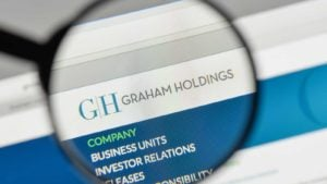 Graham Holdings (GHC) logo under magnifying glass in web browser