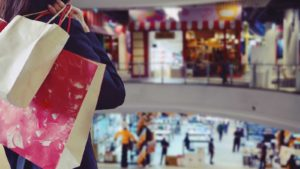 a person standing in a shopping mall with a bag in their hand