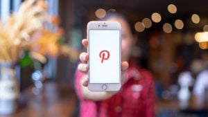 the pinterest (PINS) logo on a mobile phone held by a woman