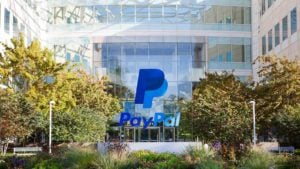 PayPal (PYPL) logo overlays daylight photo of corporate building. tech stocks
