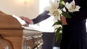 mourner laying their hand on a casket
