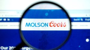 Molson Coors (TAP) logo on a web browser magnified by a magnifying glass