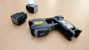 A police issued Taser X26 stun gun and two cartridges are displayed on a table for inspection.