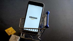 Amazon (AMZN) logo appearing on phone in miniature shopping cart