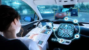 A young woman reads a book while behind the wheel of a self-driving car.