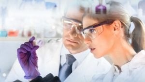 Image of two scientists in lab coats studying results in a lab