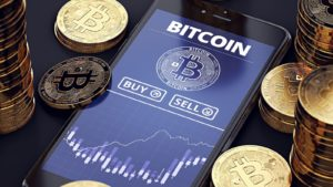 Smartphone with Bitcoin chart on-screen among piles of Bitcoins