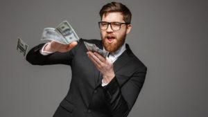 A young man throwing dollar bills.