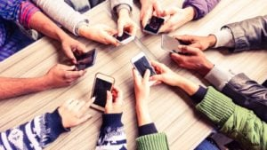 A group of people all holding cellphones sit at a table in a circle.