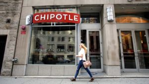a pedestrian walks past a Chipotle (CMG)