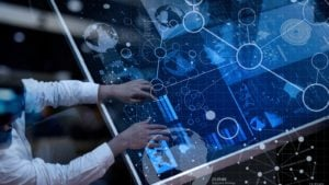 a stock image of a person working on data charts using a futuristic computer.