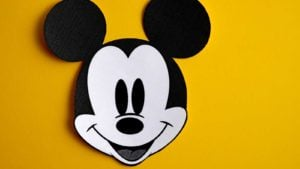 Disney (ticker: DIS) black and white Mickey Mouse against yellow backdrop