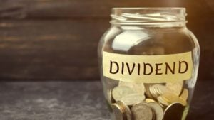 """Glass jar of coins marked """"dividends"""" to represent dividend stocks. stocks with dividends"""