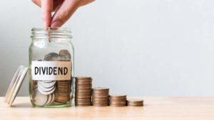 Hand putting coin in jar word dividend with money stack representing dividend stocks