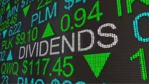 "A stock market ticker tape projects the word ""DIVIDENDS"" in white text. representing dividend stocks to buy"
