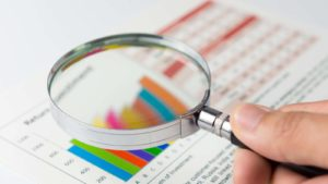 a person uses a magnifying glass to examine charts of financial data