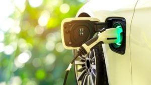 An electric vehicle is hooked up to a charging cable.