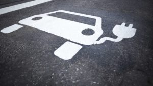 White chalk on pavement shows a plug-in electric vehicle.