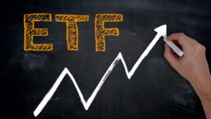 "A person drawing a line graph with the phrase ""ETF"" in large letters on a chalkboard. index funds to buy"