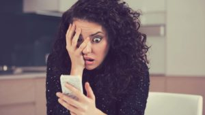 a woman looking at her phone in shock