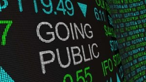 """Going Public"" is displayed in white text on a digital ticker tape."