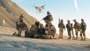 a group of soldiers in the desert with a drone flying over their heads