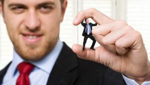 A giant business man crushing a smaller businessman between his fingers