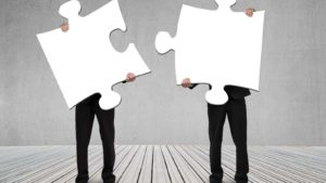 spac stocks two business people holding giant puzzle pieces, representing mergers and SPACs