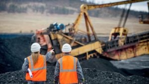 construction workers point at mining equipment in the near distance