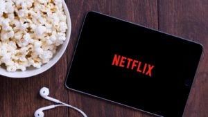 The Netflix (NFLX) logo on a tablet with earbuds and a bowl of popcorn nearby.