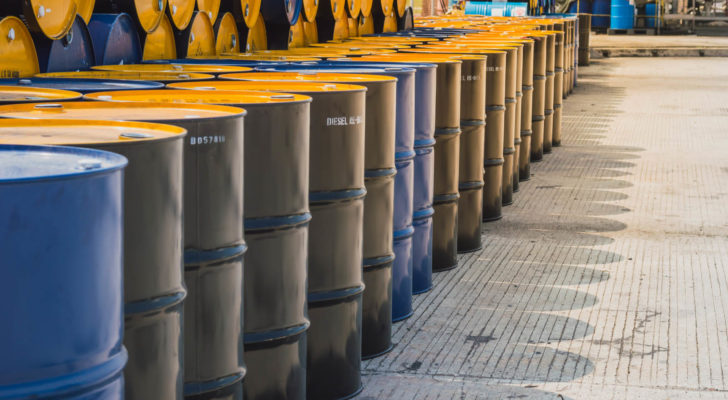 a bunch of oil barrels are stacked high