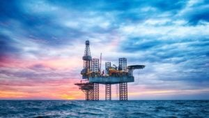 a picture of an oil rig in the middle of the ocean on a cloudy day
