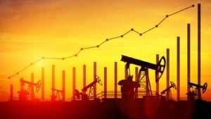Illustration of oil pump jacks on sunset sky background to represent oil and gas stocks