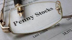 glasses over a paper reading penny stocks to buy