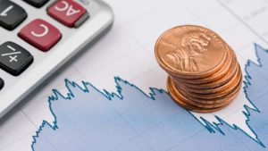 a stack of pennies and a calculator lay stop a graph of market movements