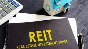 Real estate investment trust (REIT) on a black notebook on an office desk.