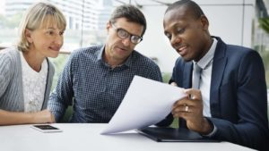 a financial planner showing a couple a piece of paper