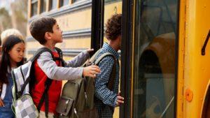children boarding a school bus, representing Education Stocks to Buy