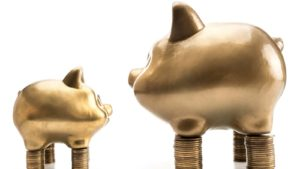 small pig figurine on top of short stack of coins next to large pig figurine on top of large stack of coins. represents small-cap stocks to buy