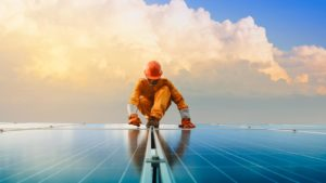 worker standing on solar panels with clouds and blue sky as backdrop