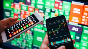 traders use smartphones to trade stocks in front of a wall of green and red tickers