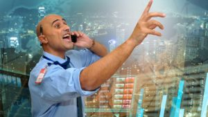man pointing at stock board to represent trading