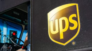 Close up of UPS logo printed on a delivery truck; partial view of the driver sitting at the wheel, waiting at a red traffic light in south San Francisco bay